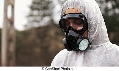 Man in gas-mask and bio-hazard suit looks down taking notes on his tablet