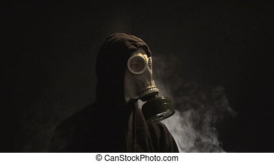 Man in Gas Mask - Smoke rising behind a man in a gas mask
