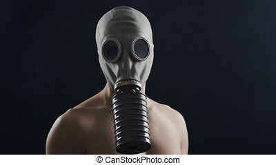man in gas mask standing in dark, with smoke around him.