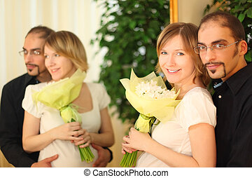 man in glasses and beauty blond girl with flowers bouquet standing near mirror and smiling