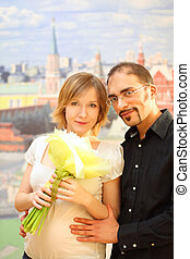 man in glasses embracing beauty blond girl with flowers bouquet, looking at camera