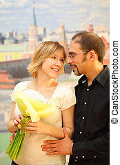 man in glasses embracing beauty blond girl with flowers bouquet, looking to each other and smiling