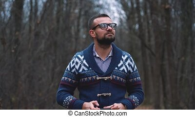 Man in glasses is walking through the autumn forest and makes photo by smartphone. Slow motion