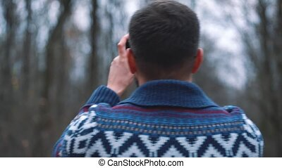 Man in glasses is walking through the autumn forest and makes photo by smartphone