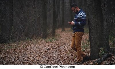Man in glasses is walking through the autumn forest and...
