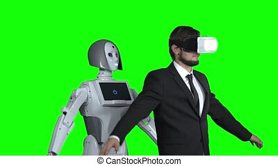 Man in glasses of virtual reality picks up the robot repeats after him. Green screen