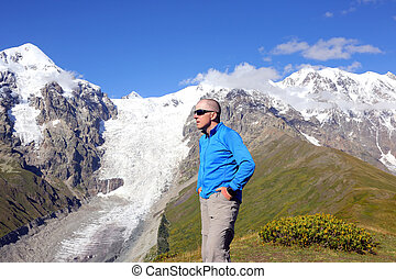 man in glasses stands on a background of snowy mountains