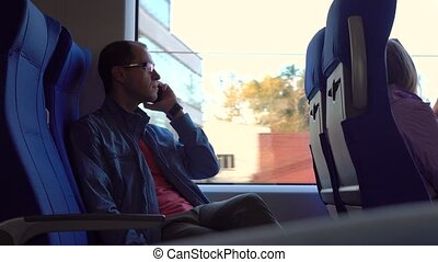 Man in glasses talking on his telephone in a modern train....