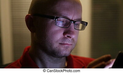man in glasses works on a tablet