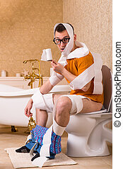 Man in glasses wrapped in toilet paper sitting on the bowl....