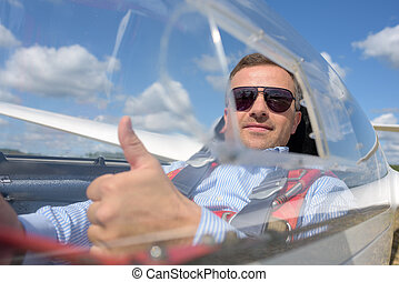 Man in glider holding up thumb
