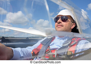 Man in glider wearing sunglasses and hat