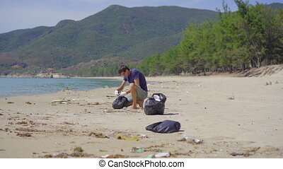 Man in gloves collects plastic trash on a beach. The problem of garbage on the beach sand caused by man-made pollution. Eco campaigns to clean the environment. Ecological volunteering concept.