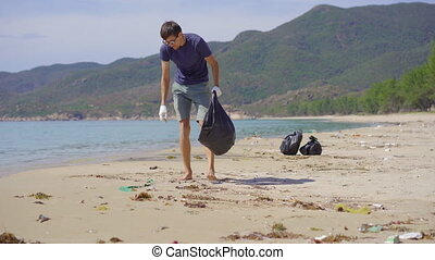 Man in gloves collects plastic trash on a beach. The problem of garbage on the beach sand caused by man-made pollution. Eco campaigns to clean the environment. Ecological volunteering concept