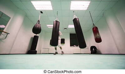man in gloves jumping around four punching bag and puts them on strikes at boxing gym, part10