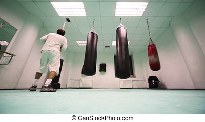 man in gloves jumps and punches on small heavy punching bag, then goes to lot of hard at boxing gym, part6