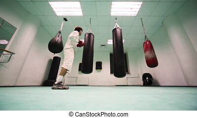 man in gloves jumps and punches on three punchbag at boxing gym, part1