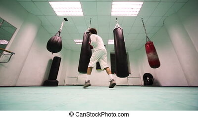 man in gloves jumps and punches on two large heavy, then light punching bags at boxing gym, part7
