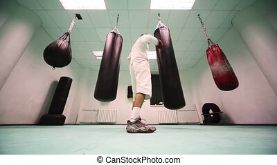 man in gloves punches big punchbag at large boxing gym