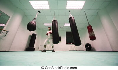 man in gloves punches by one on two small and large heavy punching bag at boxing gym, part9