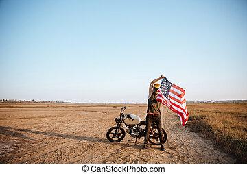 Man in golden helmet holding american flag at the desert