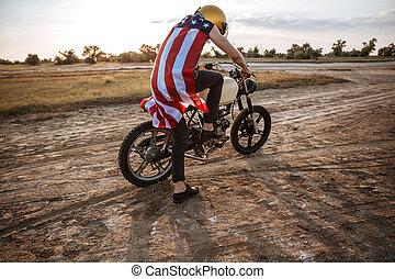 Man in golden helmet starts his motorcycle