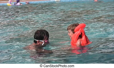 man in googles and girl has fun in swimming pool