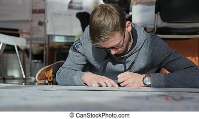 Man in gray sportswear lies on floor and creates drawing of plan of building.
