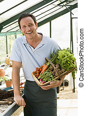 Man in greenhouse holding basket of vegetables smiling