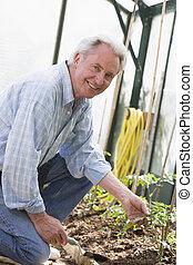 Man in greenhouse holding shovel smiling