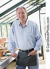 Man in greenhouse smiling