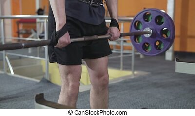 Man in Gym lifts the barbell, muscle training with weights, powerlifting.