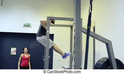 Man in gym working out, doing pull-ups on horizontal bar.