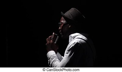 Man in half of the turnover at the microphone professionally singing. Black background. Silhouette. Slow motion. Close up
