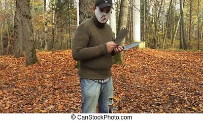 Man in Halloween mask and with two knives