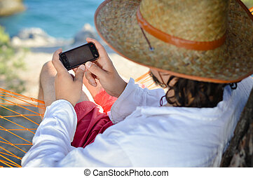 Man in hat in a hammock typing on touch phone screen on a summer day