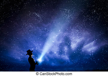 Man in hat throwing light beam up the night sky full of...