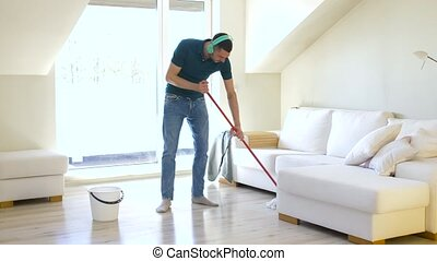 man in headphones cleaning floor by mop at home - people,...