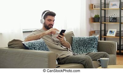 man in headphones listening to music on smartphone - ...