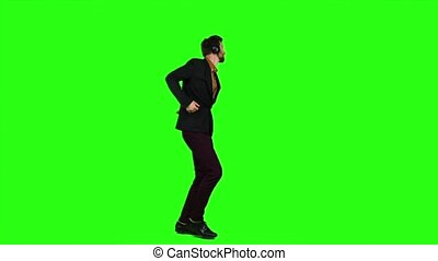 Man in headphones listens to music, dances and sings a song. Green screen. Slow motion