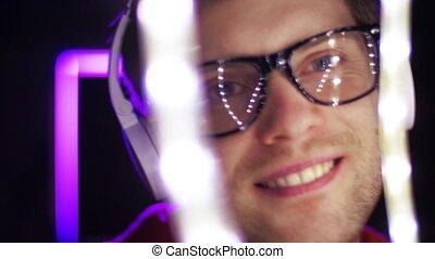 man in headphones over neon lights of night club - music,...