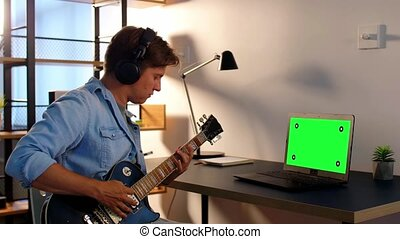 leisure, music and people concept - young man or musician in headphones with green chroma key screen on laptop computer playing bass guitar sitting at table at home