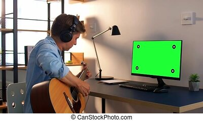 man in headphones playing guitar at home - leisure, music ...