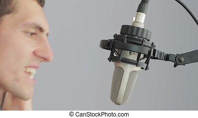 Man in headphones singing at studio microphone.
