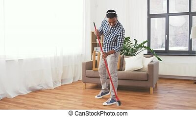 man in headphones with broom cleaning at home - cleaning,...