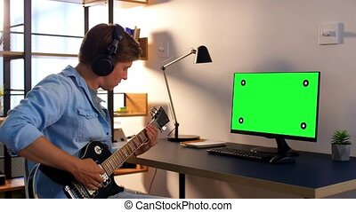 man in headphones with computer playing guitar - leisure, ...