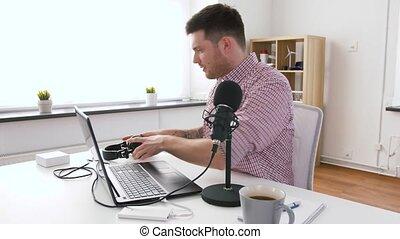 man in headphones with laptop speaks to microphone