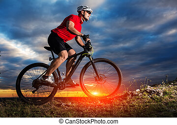 Man in helmet and glasses stay on the bicycle under sky with...