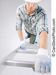 man in helmet and gloves climbing ladder - interior design...