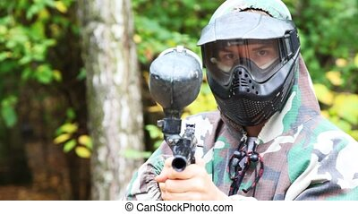 man in helmet and mask with paintball gun aims in camera